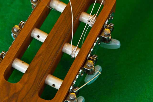 The A string is threaded on the tuning pegs of a classic guitar