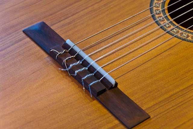 The bridge of a classic guitar with strings